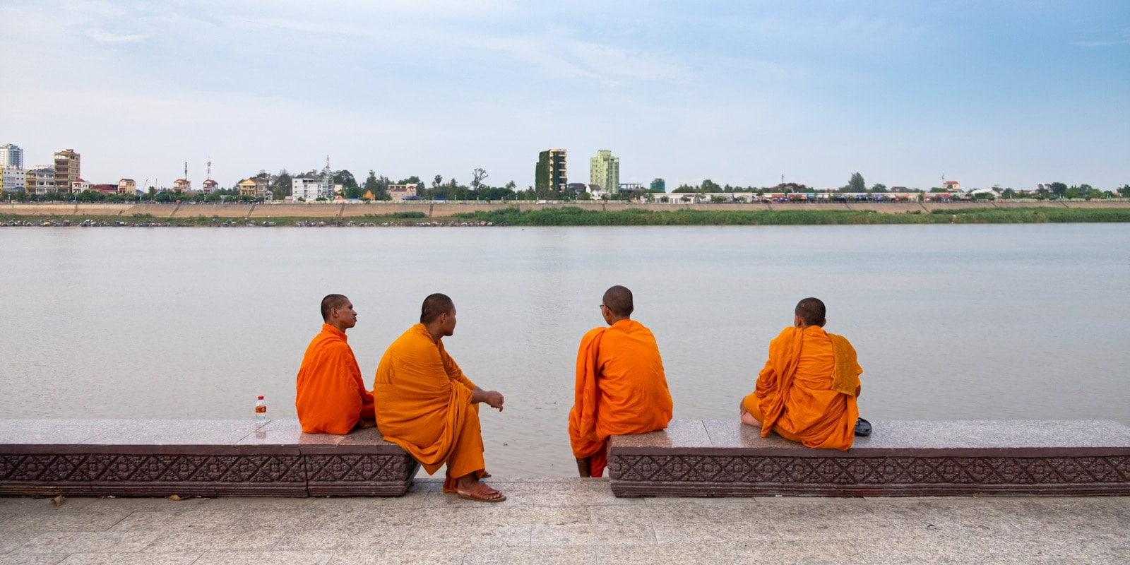 Four Buddhist monks by Phnom Penh riverside. Phnom Penh, Cambodia. Travel photos of Cambodia.