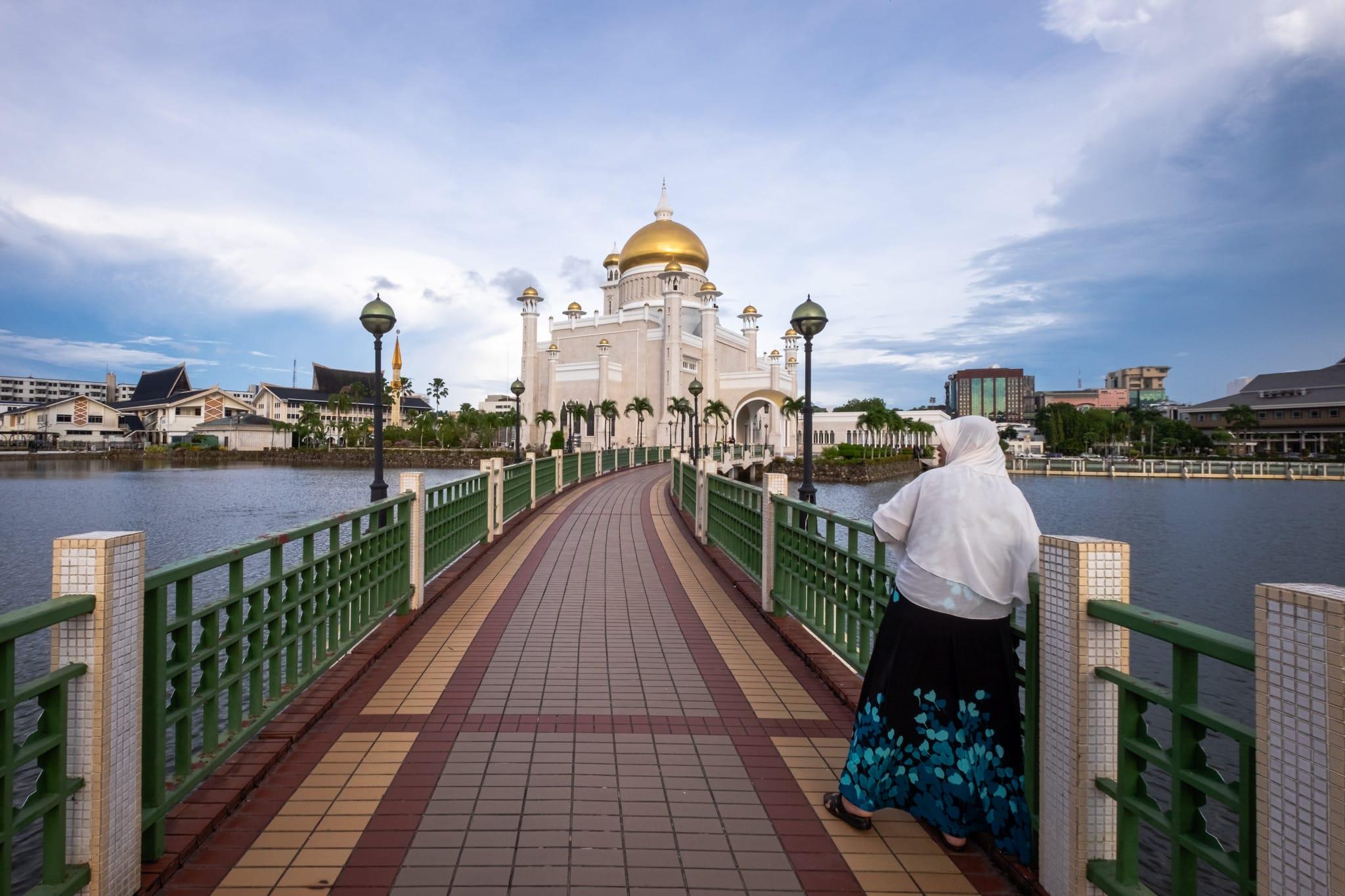 Follower of Islam on the bridge of the Sultan Omar Ali Saifuddien Mosque. Bandar Seri Begawan, Brunei.