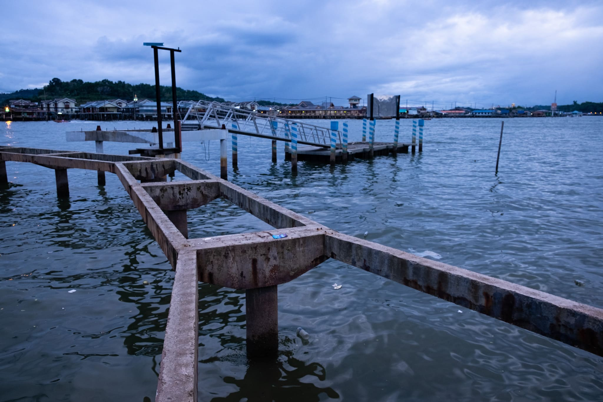 Old and broken pier in a littered waterfront of Bandar Seri Begawan, Brunei.