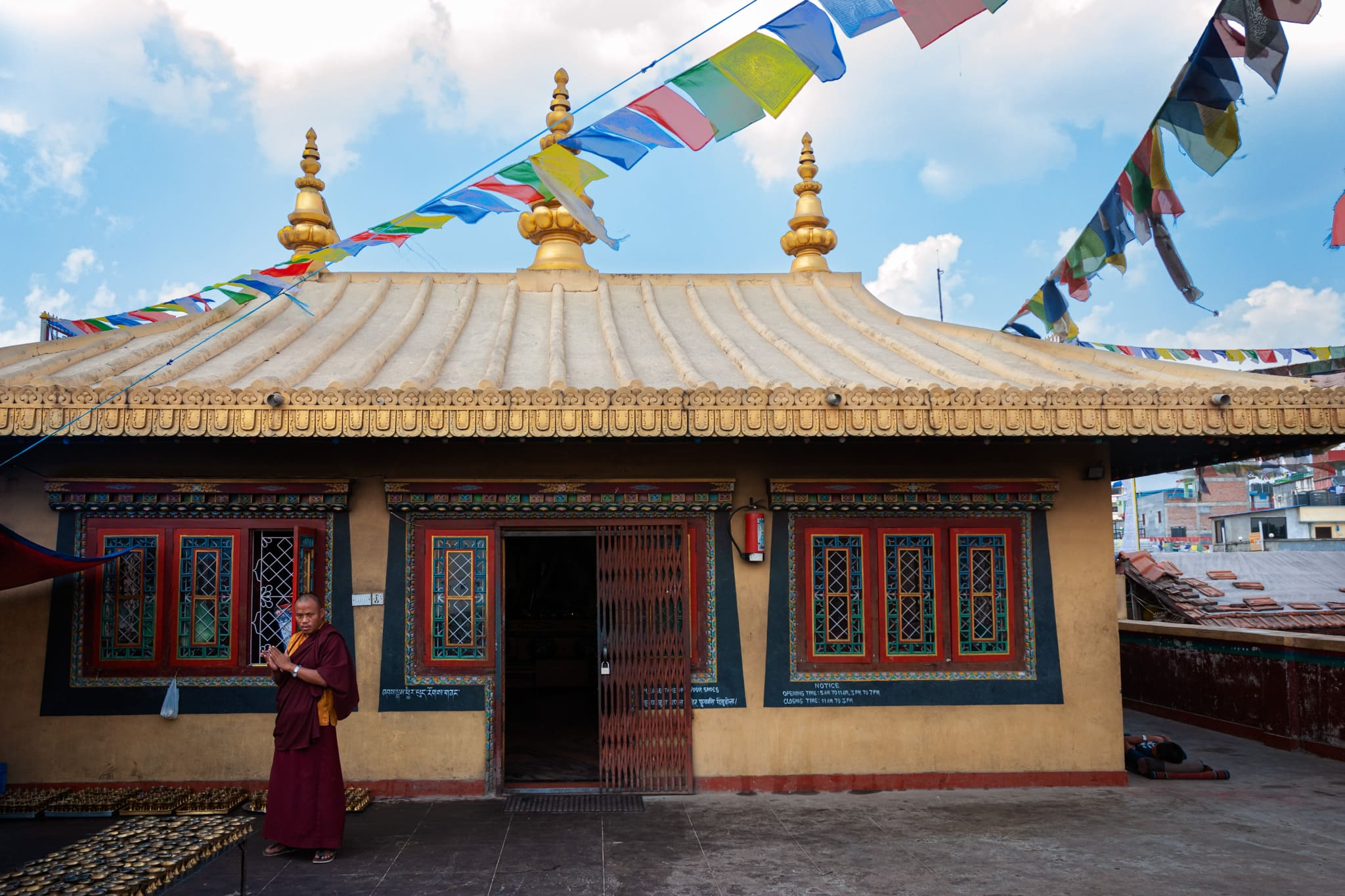 A Buddhist monk is in front of a Buddhist Monastery near Boudhanath Stupa. Kathmandu, Nepal.