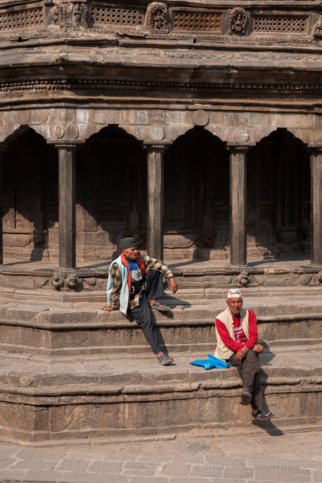 Two Nepalese men seat on the stairs of an ancient Pagoda in Patan Durbar Square. Kathmandu Valley, Nepal.