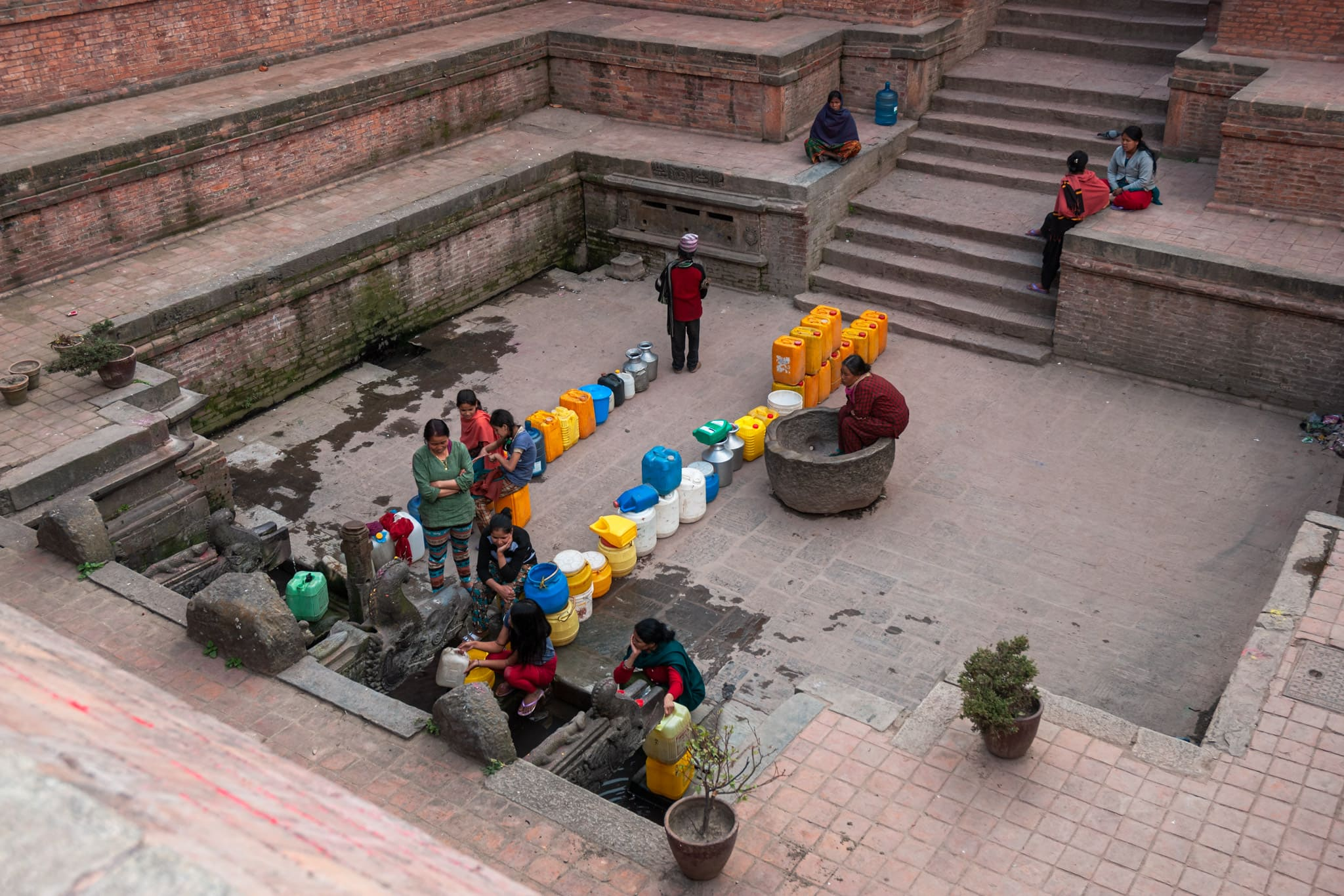 Nepalese women at the well in Patan Durbar Square collect water with colourful tanks. Kathmandu, Nepal.