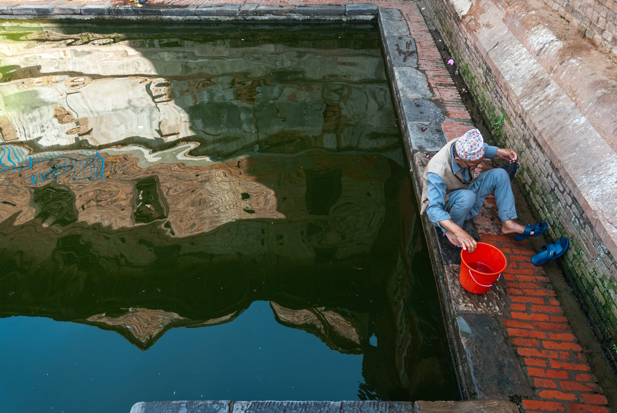 Nepalese man by a rectangular pool in Bhaktapur. Kathmandu Valley, Nepal.