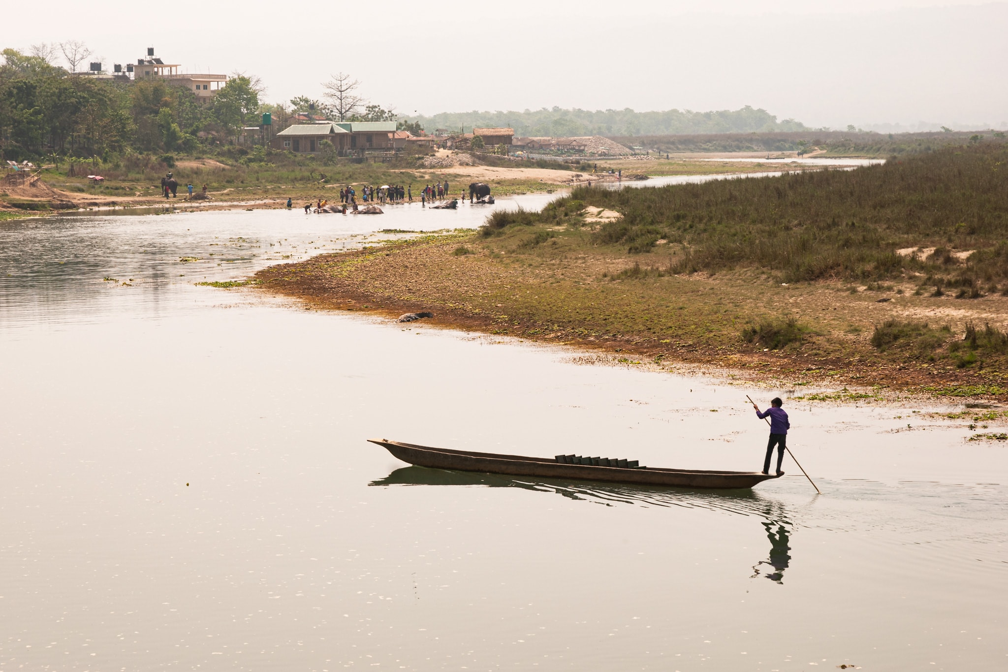 Young man on his canoe on the Narayani River. Chitwan National Park, Nepal.