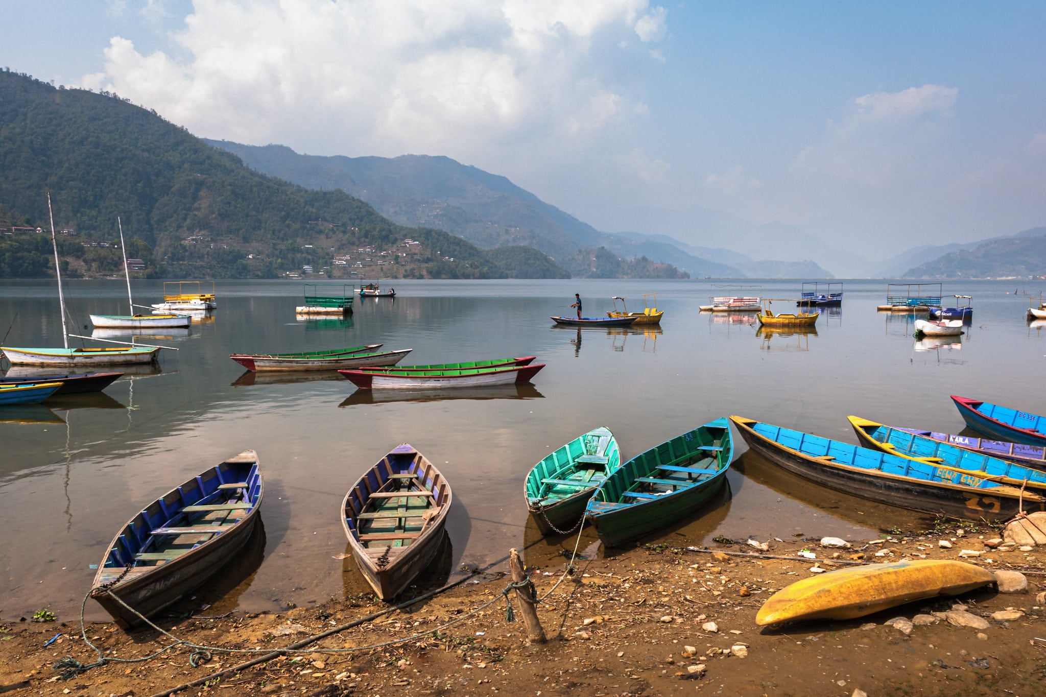 Canoes stand still at Phewa lake while a fisherman tries to catch a fish. Pokhara, Nepal.