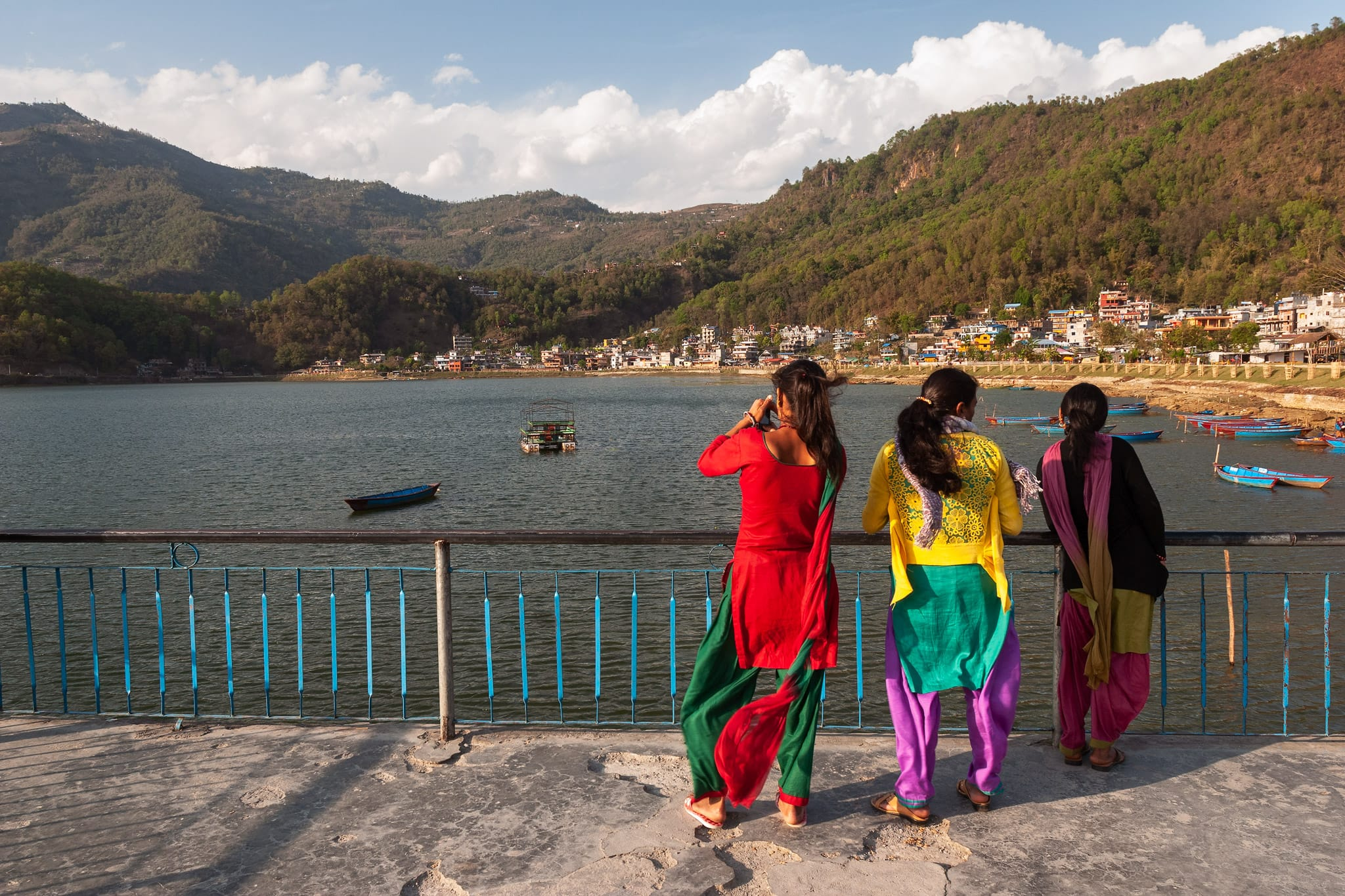 Nepalese women in colourful dresses enjoy the view at the peer on Phewa lake. Pokhara, Nepal.