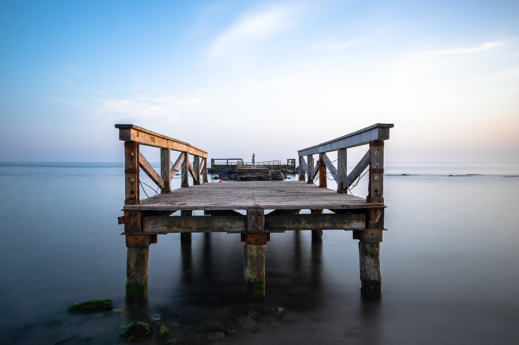 Long exposure of Fishermen Pier. Lido (Shore) di Ostia. Rome, Italy. Sea water and clouds look smooth and silky.