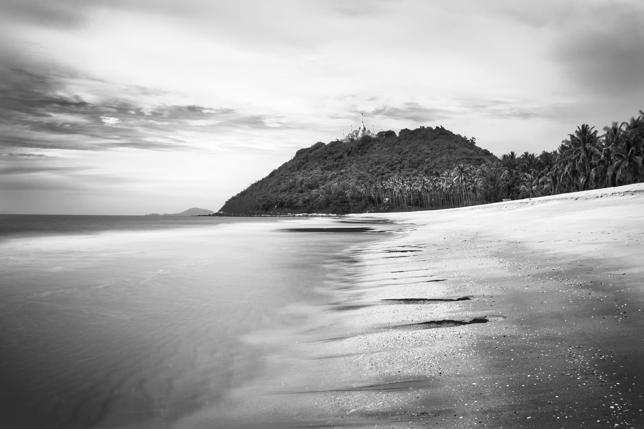 Black & white long exposure of Wat Tang Sai temple on Thongchai Mountain seen from Baan Krut beach, Thailand.