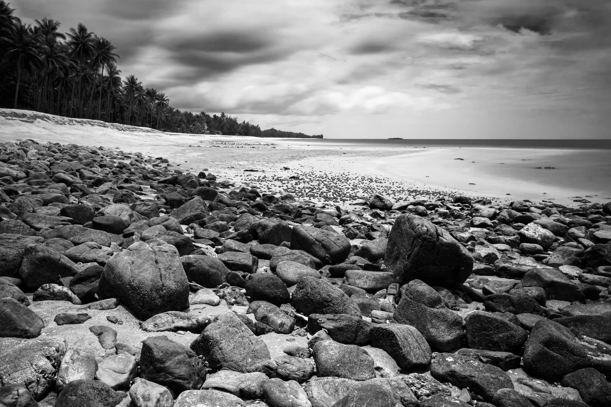 Black and white long exposure of Baan Krut beach, Thailand. Stones on the foreground.