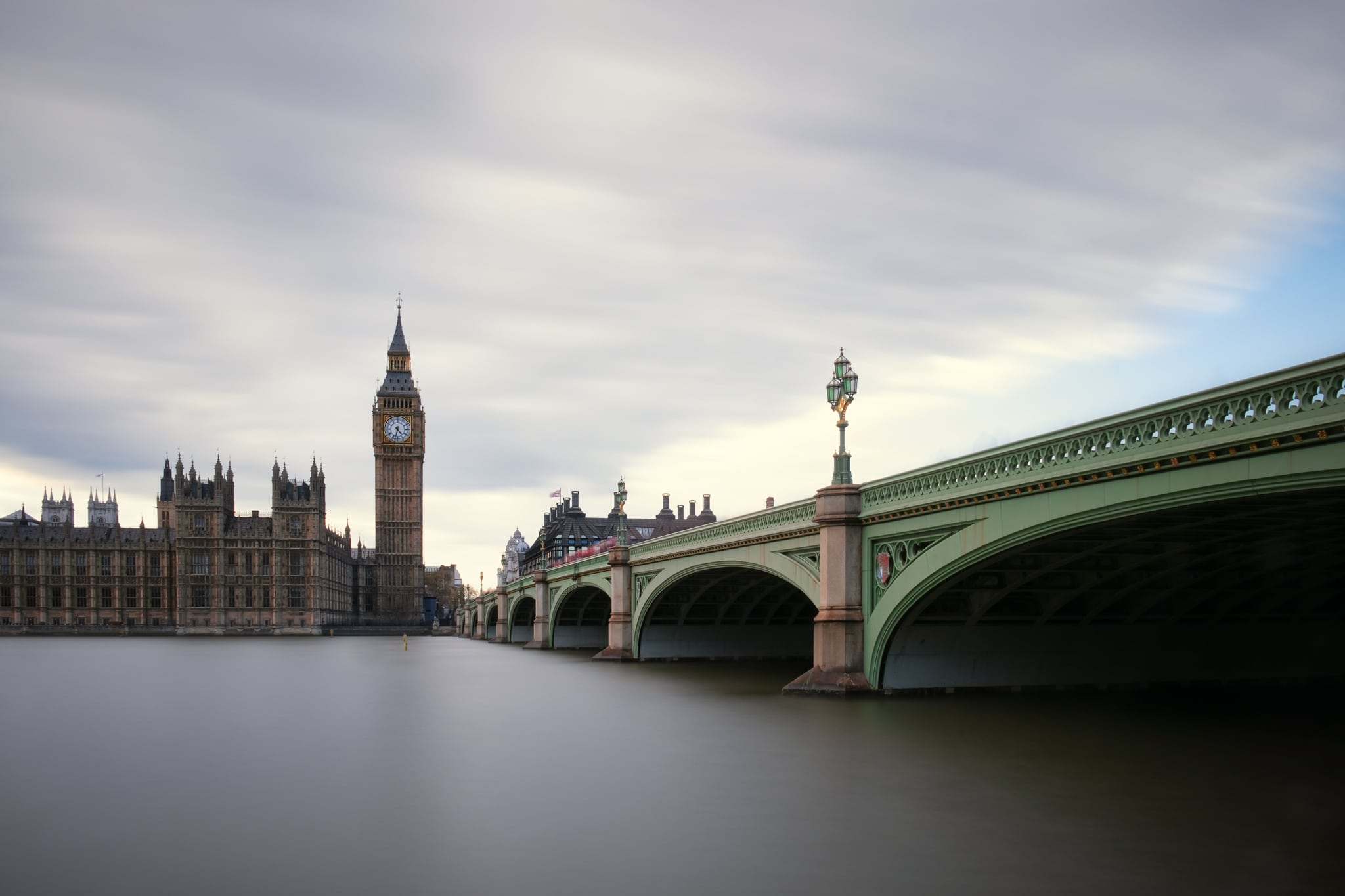 Westminster Bridge with the Palace of Westminster and the Big Ben. London, Uk. Because of the long exposure water and clouds look smooth and silky, and people look ghostly almost disappeared.