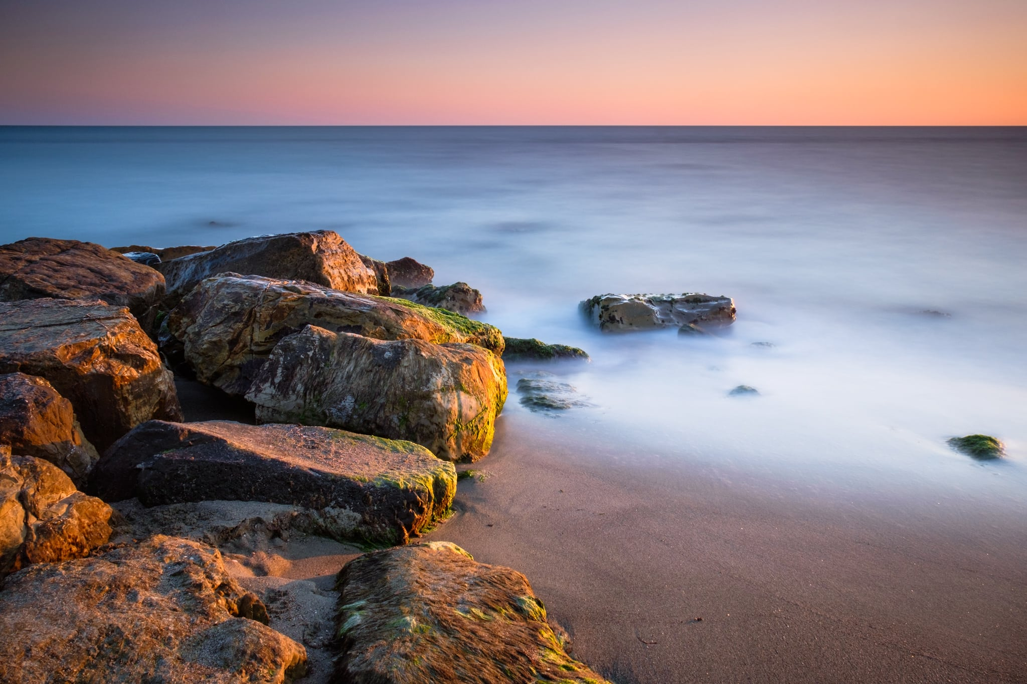 Long exposure photography ideas of rocks on the shore at sunset. Sea water looks smooth and silky.
