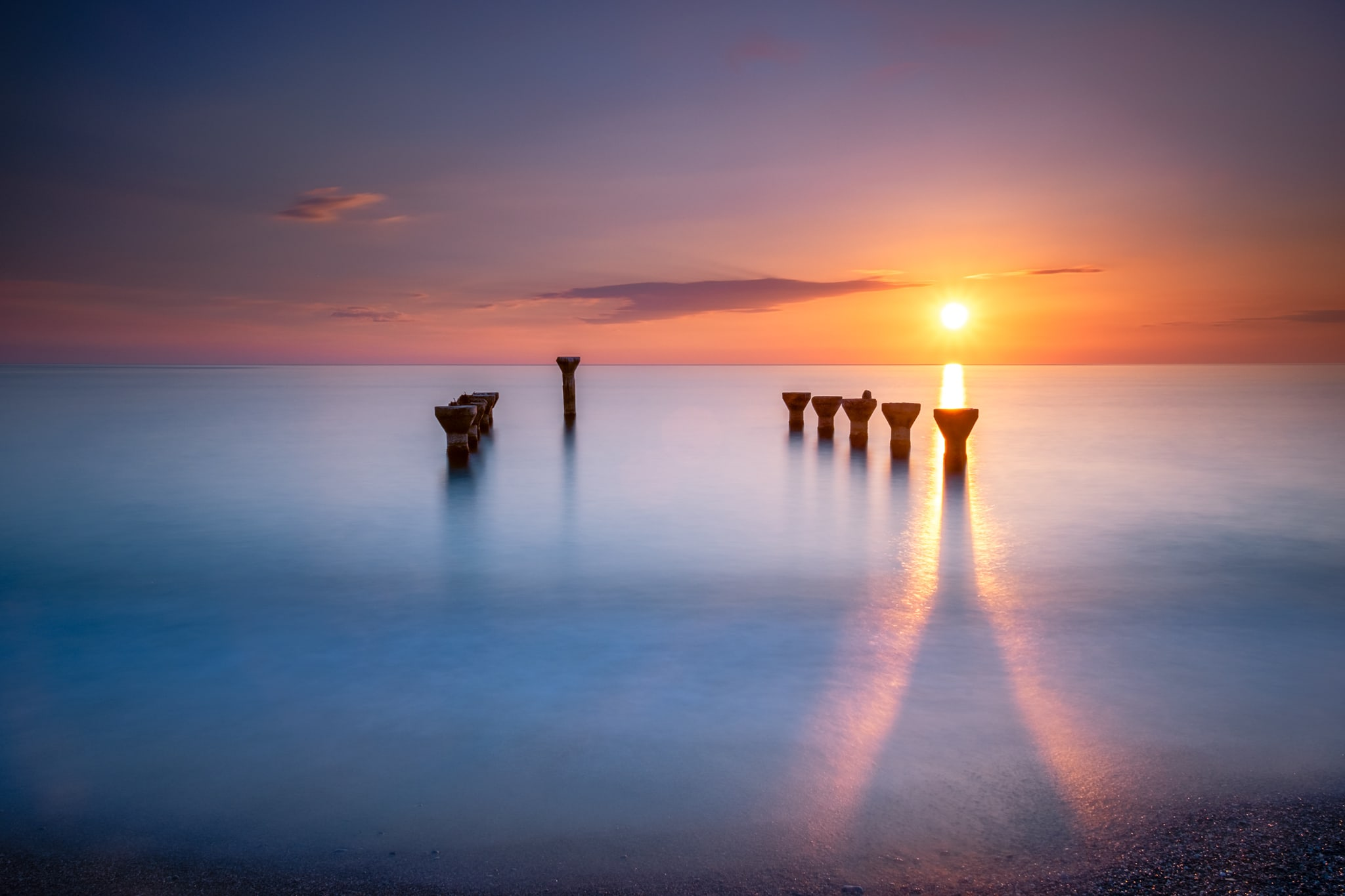 Long exposure photo of remains of a pier at sunset. Lido di Paola, Cosenza, Italy. Sea water is silky and smooth.