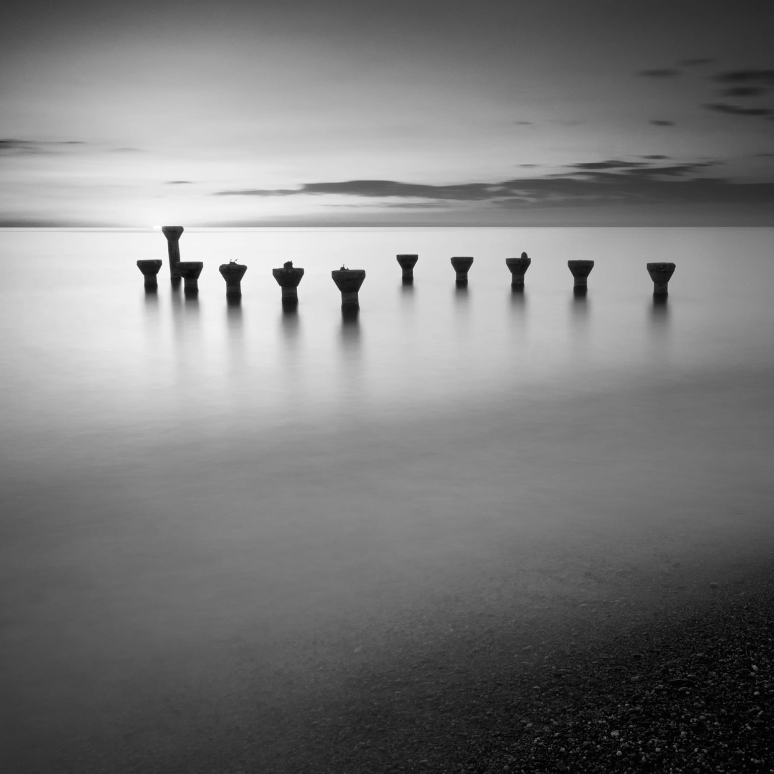Black and white long exposure image of remains of a pier at sunset at Lido di Paola. Cosenza, Italy. Sea water and clouds look smooth and creamy.