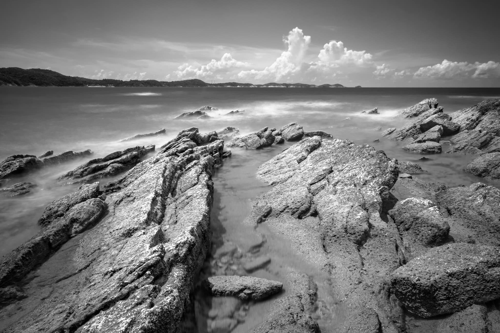 Black & white long exposure of rocky beach at Ban Phe. Rayong, Thailand. Smooth and silky sea water in contrast with rocky beach.