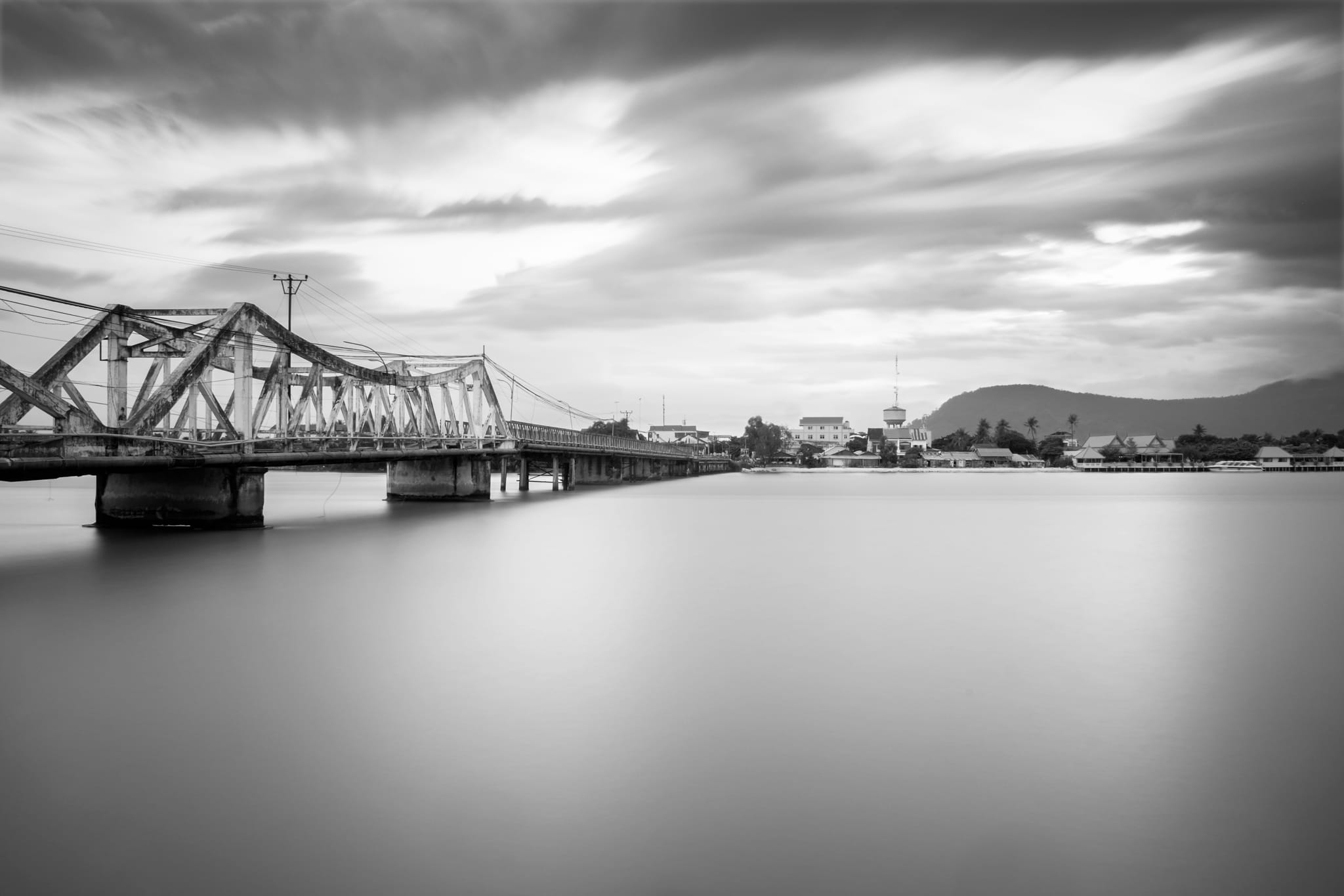 Long exposure of the old French bridge over Kampot River in B & W. Kampot, Cambodia. Clouds and water look very smooth and silky.