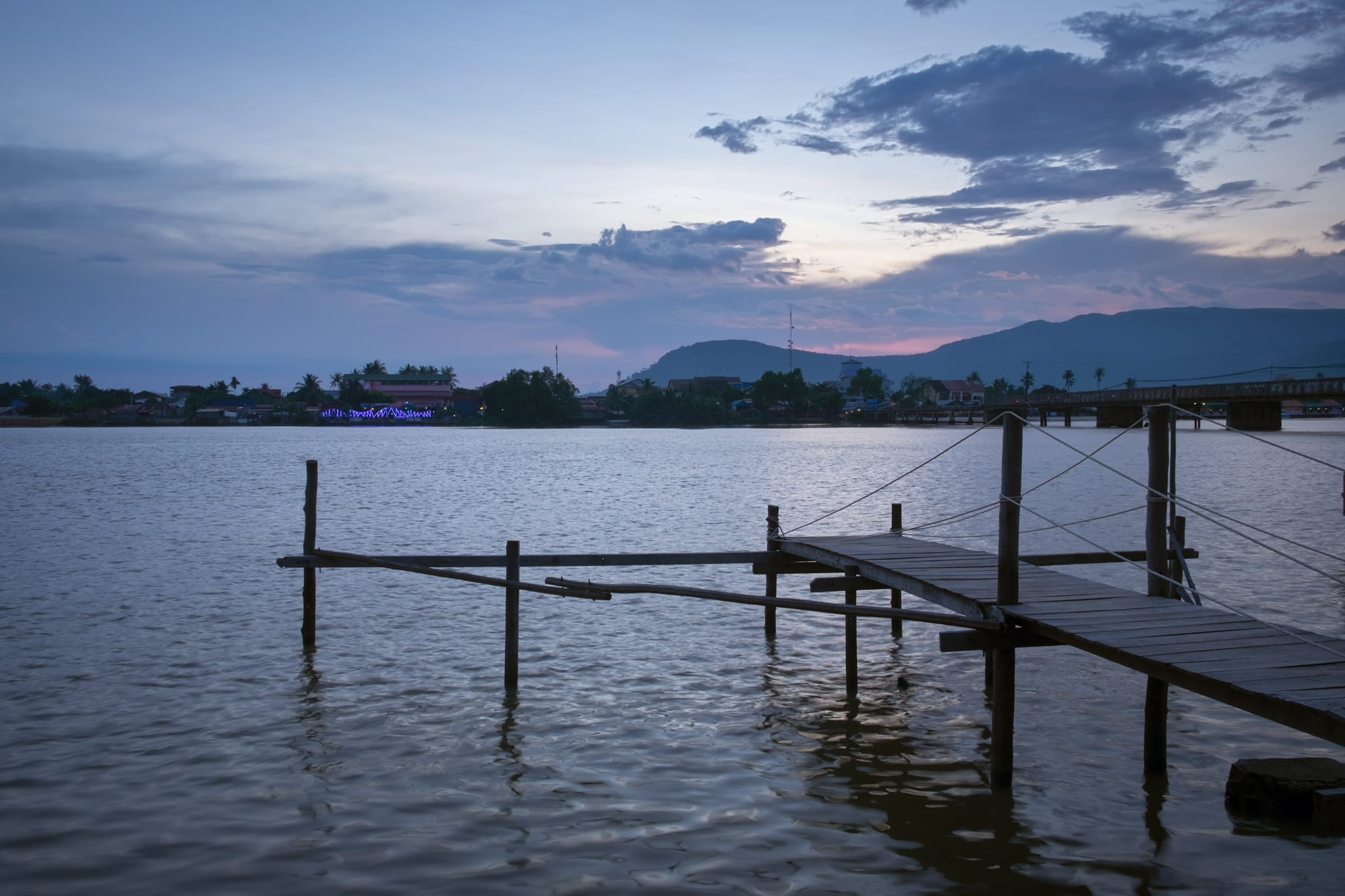 Wooden pier on Kampot River in twilight. Kampot, Cambodia.