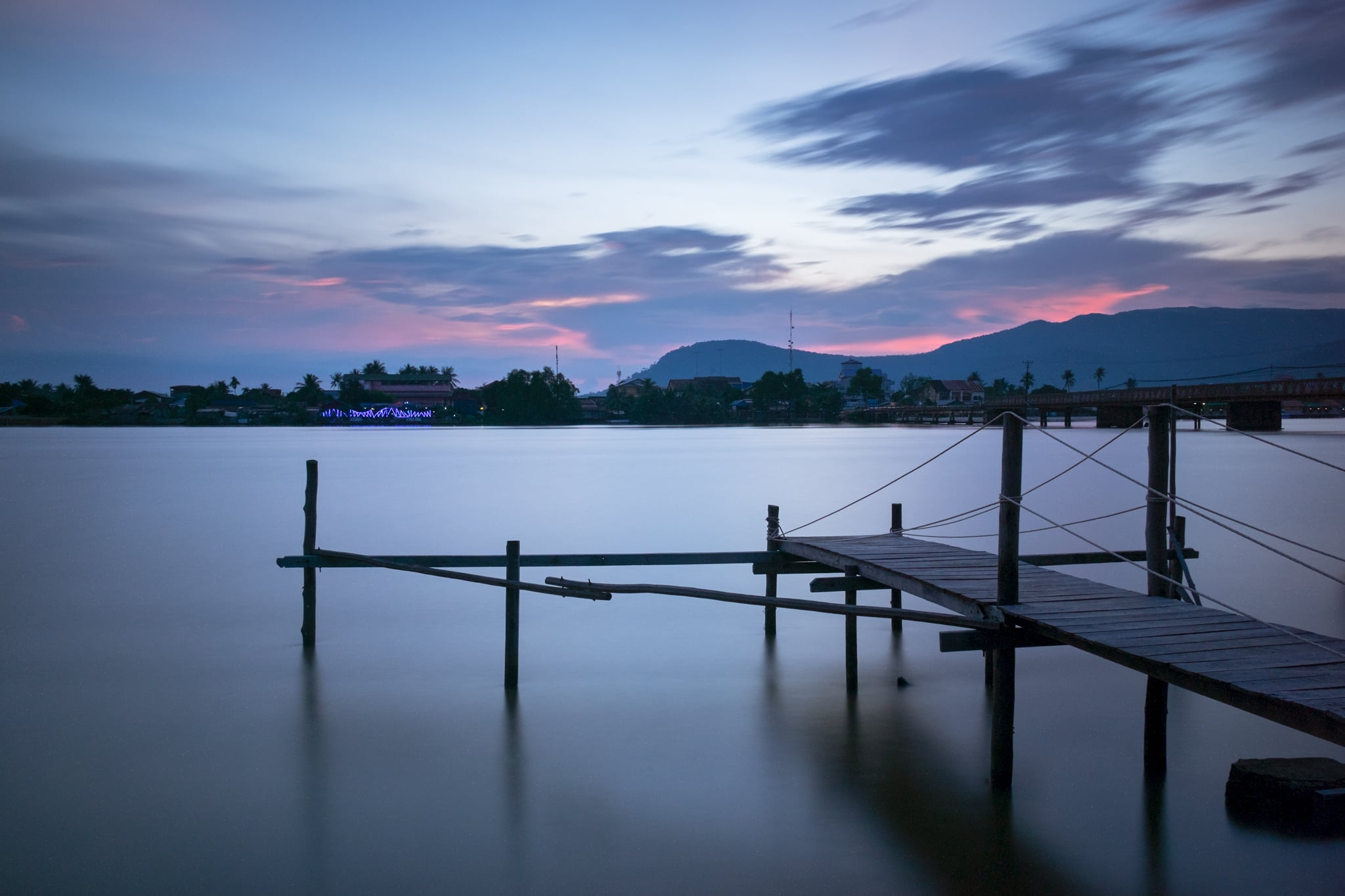 Wooden pier on Kampot River in twilight. Kampot, Cambodia. Water and clouds look smooth and silky because of the long exposure.