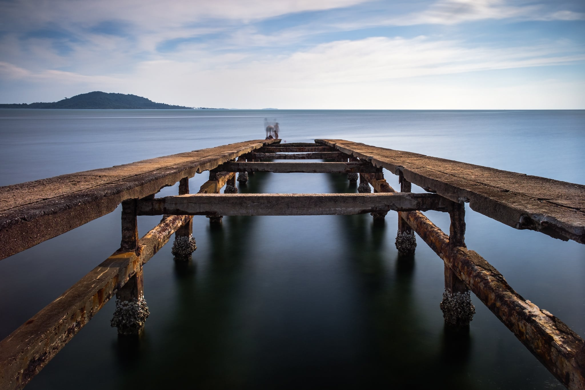 Long exposure of old pier. Kep Beach, Cambodia. Sea water and clouds look smooth and creamy. People on top of the pier are motion blurred, ghostly like.