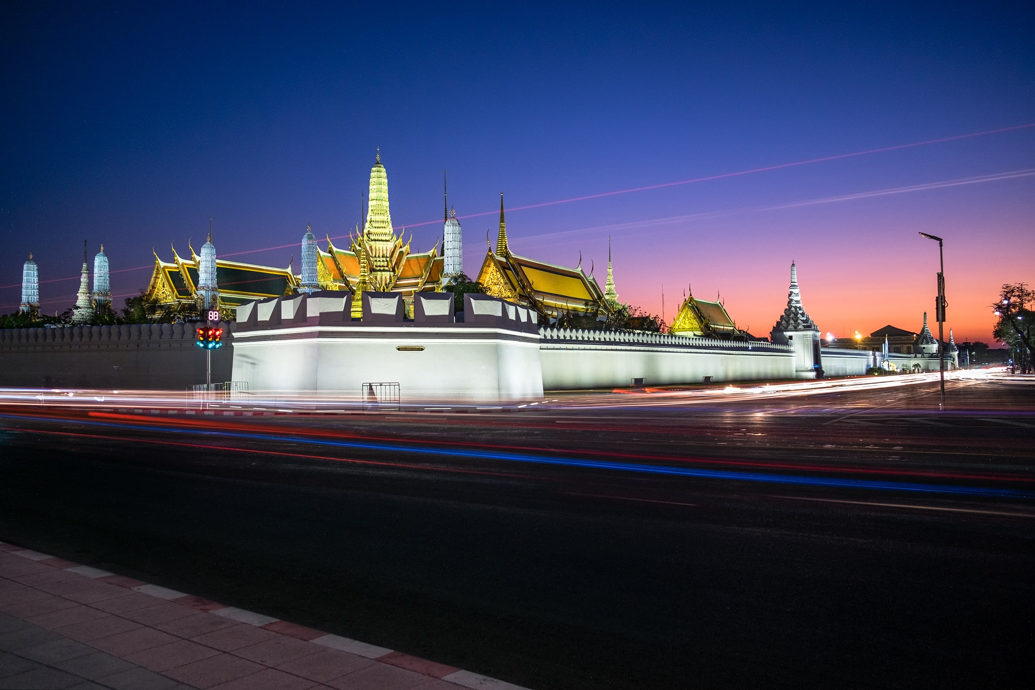 Light trails from cars in front of the Grand Palace in twilight. Bangkok, Thailand.